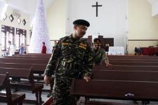 Dua Anggota Banser tengah memeriksa bangku-bangku di sebuah gereja menjelang perayaan Natal